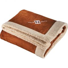 A tan coloured sherpa blanket with a white embroidered logo in one corner