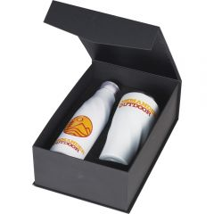 An angled view of a matte black gift box open to show a white copper vacuum 22oz bottle and 20oz tumbler both with red and yellow logos