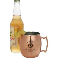 A 16oz copper and stainless steel moscow mule mug with black and orange logo in front of a bottle of beer