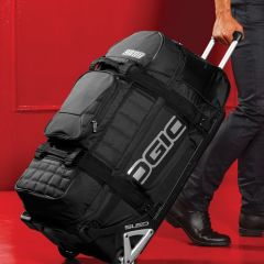 A lifestyle shot of a stealth coloured wheeled rig bag being pulled with the handle extended in front of a red door