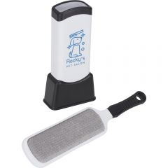 An angled view of a black and white pet hair remover double sided brush and the same coloured holder with a blue logo on the front behind it