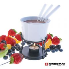 A white ceramic fondue bowl filled with chocolate and the forks are inside. The bowl is on a metal stand with a light below and surrounded by fruit