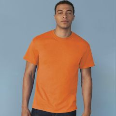 A safety orange coloured round neck heavy cotton T-Shirt being worn by a man stood in front of a blue wall
