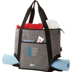 An angled view of a graphite fitness tote with black accents and a grey and blue logo. The bag has a blue yoga mat through it and is filled with clothing at the top