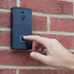 A smart WiFi video doorbell mounted to a brick wall with a finger touching it
