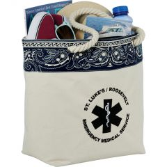 A natural coloured cotton tote filled with goods and with navy detailing and a black logo