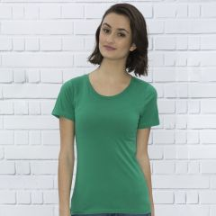A kelly green coloured ring spun round neck ladies tee veing worn by a woman with medium brown hair stood in front of a grey brick wall