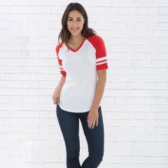 A white and red ring spun V neck ladies baseball tee being worn by a model with long brown hair and one hand in her pocket stood in front of a grey brick wall
