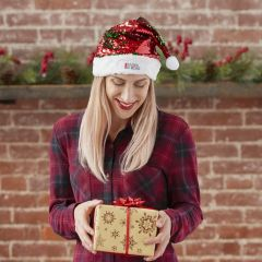 A woman with blonde hair in a red plaid sweater holding a gold coloured gift box with a red ribbon. On her head is a red and green sequin Santa hat with a red and black logo on the trim. She is stood in front of a brick wall background with a wooden shelf