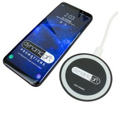 circle shaped black and white phone charge pad with phone beside it