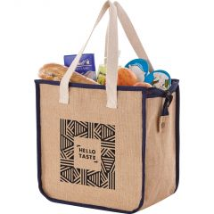 An angled view of a light brown jute insulated grocery tote with navy trim, cream handles and a black logo. The bag is filled with groceries.