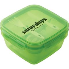 An angled view of a green translucent square salad container with the plastic cutlery and dressing container inside and a black logo on the lid