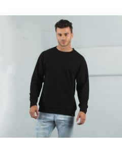 An onyx coloured cotton and polyester crewneck fleece being worn by a short haired man leaning against the corner of a wall
